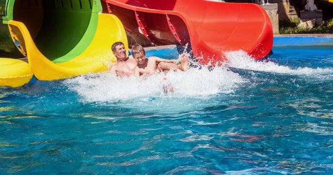 Happy family enjoying the water park slide