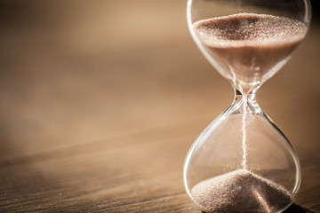 Sand running through the bulbs of an hourglass measuring the passing time in a countdown to a deadline with copy space.