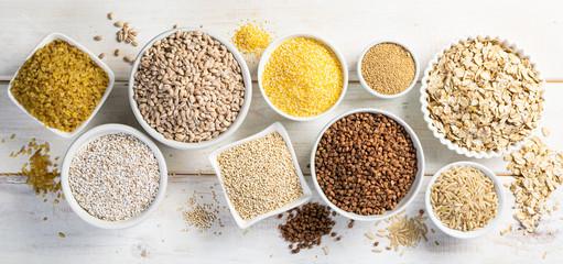 Selection of whole grains in white bowls - rice, oats, buckwheat, bulgur, porridge, barley, quinoa, amaranth, on white wood background