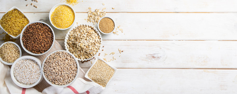 Selection of whole grains in white bowls - rice, oats, buckwheat, bulgur, porridge, barley, quinoa, amaranth, on white wood background