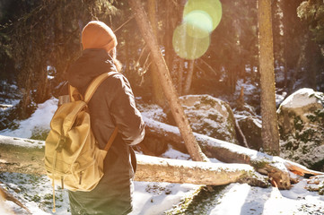 A bearded man in a hat and a backpack stands with his back on a sunny day in winter in a coniferous forest. The concept of winter travel and walks in the woods