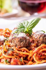 Spaghetti mit Fleischbällchen auf dunklem Holz