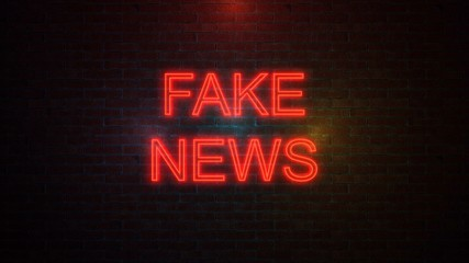 The word FAKE NEWS with neon colours on brick wall.