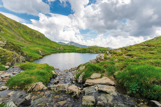 lake capra of romanian fagaras massif. beautiful alpine scenery of carpathians in summer. clouds on the blue sky. grass and boulders on the slopes. stream runs down the rocks