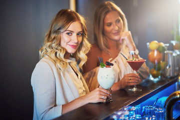 Two girl friends having drinks in bar