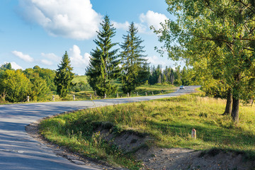 old serpentine road uphill through forest. beautiful transportation evening scenery. fluffy clouds on the azure sky. cracked asphalt and gravel roadside.