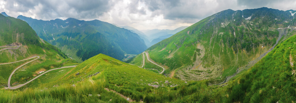 panorama of transfagarasan serpentine road. beautiful summer landscape on an overcast day. steep slopes with grass and rocks. popular travel destination of romania