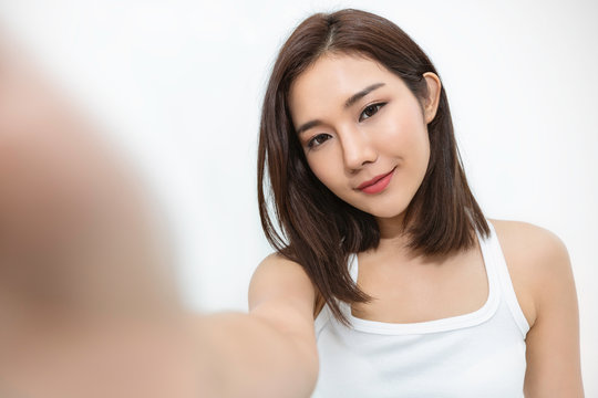 Portrait of young beautiful asian woman using smart phone selfie live in white bedroom.Happy asian girl online influencer blogger. Education e-commerce technology connected people lifestyle concept