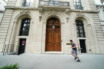 A man runs past the front door of the upper east side home of Jeffrey Epsteinin New York