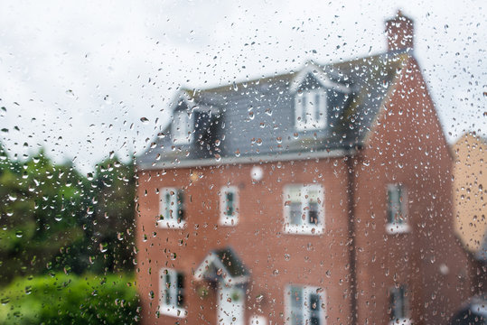 Detached red family house viewed through a glass window covered in rain water drops