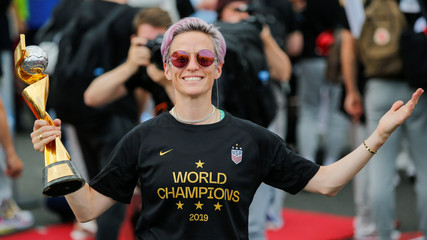 Megan Rapinoe, smiles as she holds the Trophy for the FIFA Women's World Cup while the U.S. team arrive at the Newark International Airport, in Newark, New Jersey