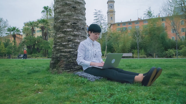 Dressed in formal business clothes. Multicultural female in city France Nice outdoor. Female sitting under a tree typing on the computer. On the background beautiful old building 19th century