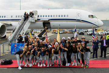U.S. women soccer players pose for a picture with the Trophy for the FIFA Women's World Cup while the team arrives at the Newark International Airport, in Newark