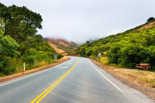 Paved road with a 35 mph speed limit going through Marin Headlands; cloudy and foggy day; Marin County, North San Francisco bay area, California