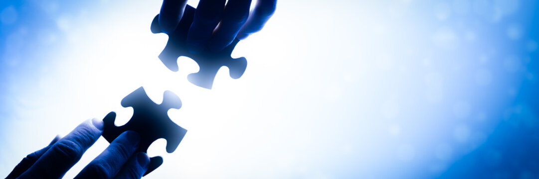 Hands Putting Puzzle Pieces Together/Business Concept