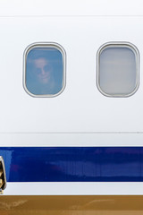 Rapinoe peeks out of a window of a United airplane while the U.S. team arrives with the trophy for the FIFA Women's World Cup at the Newark International Airport, in Newark, New Jersey