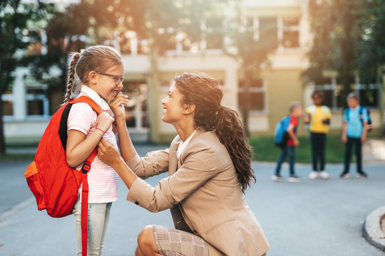 First day at school. Mother leads a little child school girl in first grade.