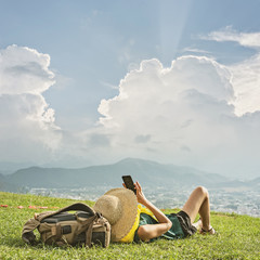 woman lie on grassland and take a picture