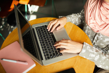 Close-up image of young woman in hijab working on laptop when sitting at table in cafe