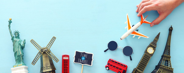 holidays image of traveling concept with accessories and world symbols over blue background. top view, flat lay