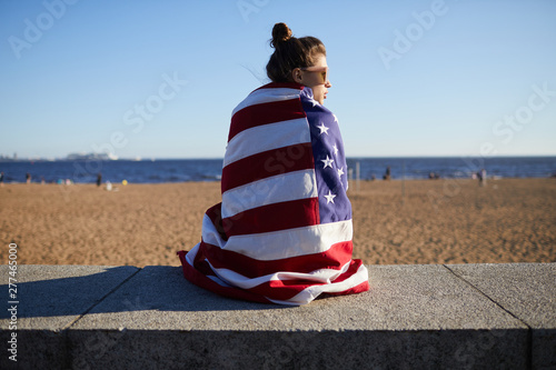 Serious pensive attractive American girl wrapped in national flag sitting on concrete slab while resting on beach