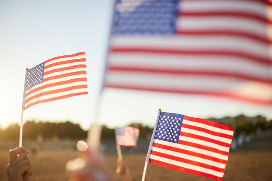 Group of unrecognizable people waving small American flags on sticks at parade outdoors
