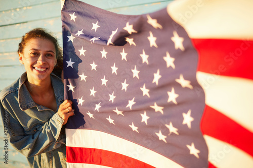 Portrait of happy attractive student girl in denim jacket proud of America holding national flag outdoors