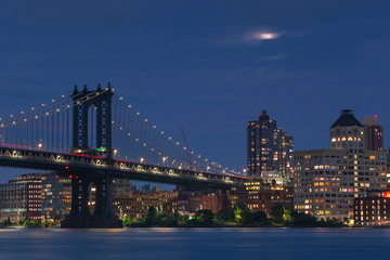Manhattan Bridge and  Dumbo from East River with full moon at night ,with long exposure photo