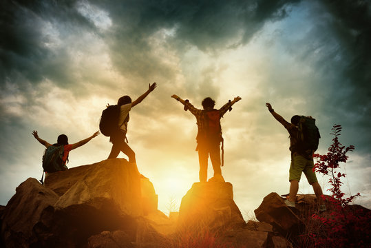 Celebrating life of Hikers climbing up mountain cliff. Climbing group helping each other while climbing up in sunset. Concept of help and teamwork, Limits of life and Hiking success full.