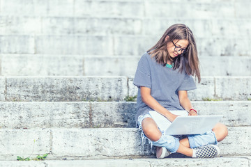Young schoolgirl sitting on stairs with laptop and watching internet or social network