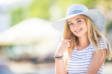 Summer portrait of young beautiful woman in hat sitting on bench in park