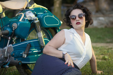 A pinup woman in a vintage dress posed next to the old motorcycle