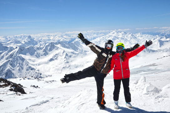 Young couple in snowboarding helmets standing at caucasus mountains, Elbrus