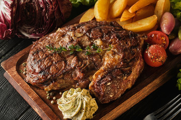 Photo sur Toile Steakhouse Ribeye steak with potatoes, onions and baked cherry tomatoes. Juicy steak with flavored butter