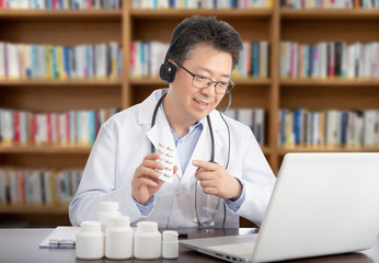 an Asian doctor who is remotely consulting with a patient. Telehealth concept