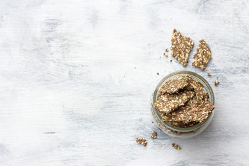 Delicious healthy multigrain gluten-free crackers, ketogenic, from chia seeds, flax, sesame and ground pumpkin seeds in a glass jar on a gray background, top view, horizontal