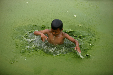 A boy takes a dip into a pond covered with algae in Bhaktapur
