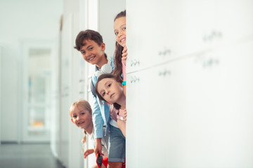 Boy and girls smiling while standing near lockers at school break