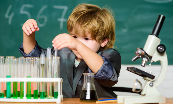 Gifted child and wunderkind. Kid study chemistry school. School education. Explore biological molecules. Toddler genius baby. Boy near microscope and test tubes in school classroom. Science concept