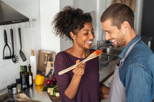 Multiethnic couple tasting food from wooden spoon