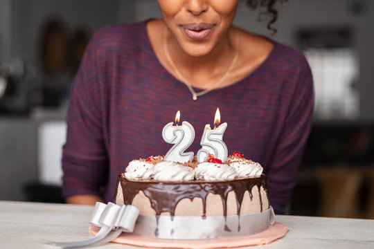 African woman blowing birthday candles on cake