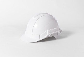 White Plastic safety helmet for engineer on gray background.