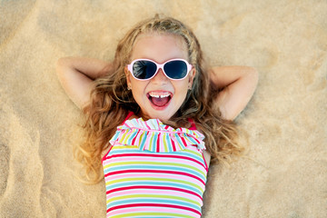 Top view of pretty little blonde girl in sunglasses lying on sandy beach during summer vacation
