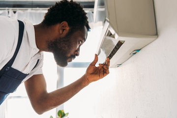 concentrated african american repairman looking at broken air conditioner Wall mural