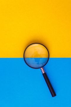 Magnifier lies on yellow and blue background. View from above. Flat lay. Copy space