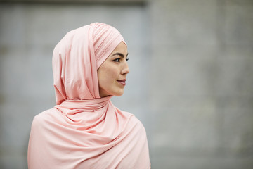 Side view of content introspective young Muslim woman of Islamic faith wearing pink hijab looking into distance outdoors