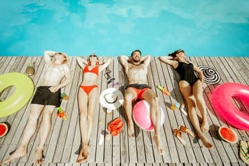 Group of a happy friends in swimwear lying on the poolside, sunbathing near the swimming pool, view from above