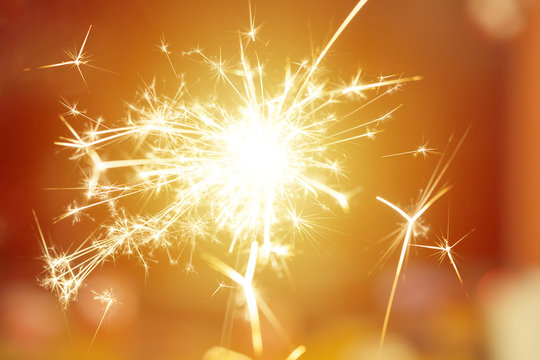 Sparks from hand cold fireworks bright sunspot background