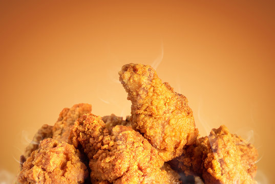 Fried chicken or crispy kentucky on brown background. Delicious hot meal with fast food.