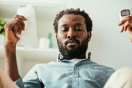 african american man with sweaty face holding napkin and remote controller while suffering from heat at home